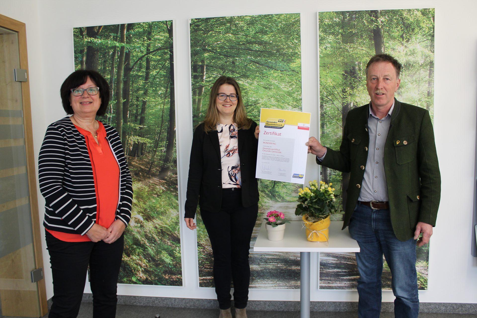 Dieses Bild zeigt v.l.n.r. Mitarbeiterin Adelheid Schicktanz, Arbeitskreisleiterin Verena Aigner und Bürgermeister Martin Voggenberger mit dem Qualitätszertifikat der Gesunden Gemeinde.